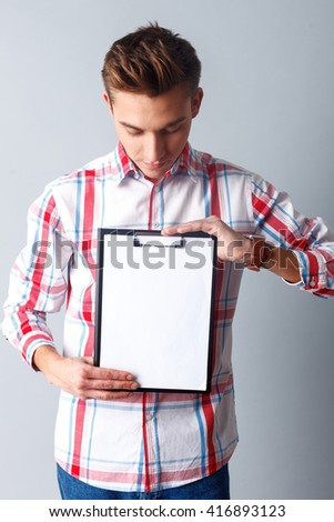 Cheerful young man is showing some papers - stock photo