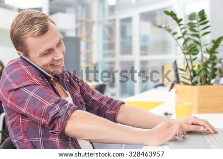 Cheerful young man is typing on laptop in open office. He is sitting at desk and talking on mobile phone. The worker is smiling - stock photo