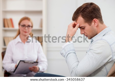 Cheerful young man is visiting experienced female psychologist. He is sitting and touching his head with frustration. The woman is looking at him with pity and writing - stock photo