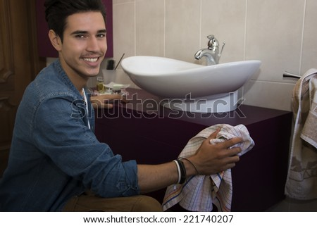 Cheerful young man kneeling down with a cloth in his hand cleaning the bathroom interior wiping the ceramic hand basin and cabinets and turning to smile at the camera - stock photo