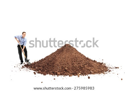 Cheerful young man shoveling a big pile of dirt and looking at the camera isolated on white background - stock photo
