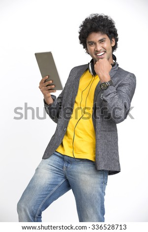 Cheerful Young Man showing success sign with Digital Tablet On White Background - stock photo