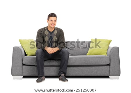Cheerful young man sitting on a modern sofa isolated on white background - stock photo