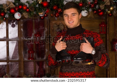 Cheerful young man wearing a sweater with seasonal pattern while holding a pair of figure skates, in front of a chalet, decorated with Christmas baubles and garlands, concept of winter vacations - stock photo
