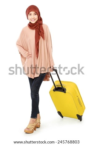 cheerful young muslim woman carrying a suitcase isolated on white background - stock photo