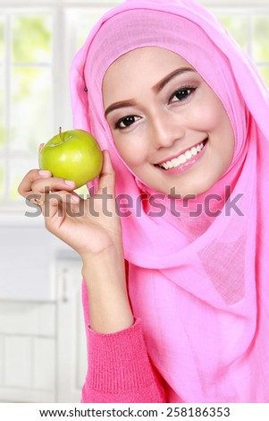 cheerful young muslim woman holding an apple - stock photo