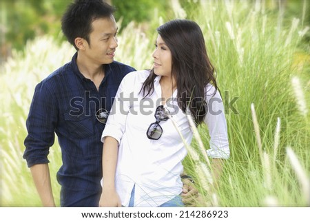 Cheerful young newlyweds hugging tenderly in bright countryside - stock photo