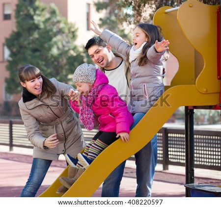 Cheerful young parents with two excited little daughters at sliding board outdoors . Selective focus - stock photo