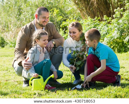 Cheerful young parents with two smiling kids planting a tree together - stock photo