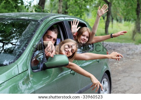 Cheerful young people having summer trip on a car. - stock photo