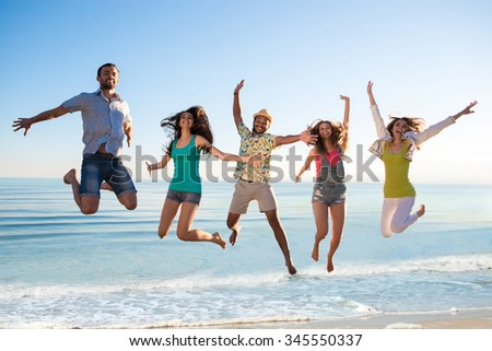 Cheerful young people jumping on the beach. Guys and girls at the resort. Weekend at sea. Rest on the ocean. Company of friends having fun on the background of the sea. - stock photo