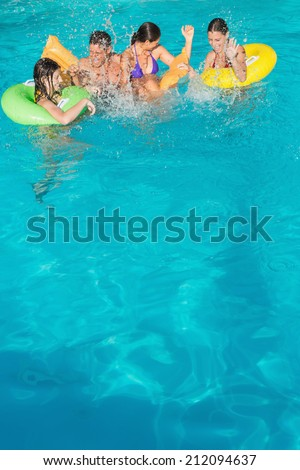 Cheerful young people playing in the swimming pool - stock photo
