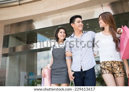 Cheerful young people with shopping bags - stock photo