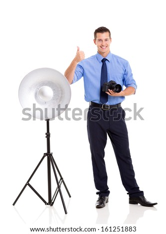 cheerful young photographer giving thumb up on white background - stock photo