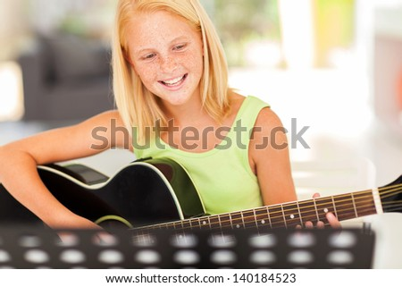 cheerful young pre teen musician playing guitar - stock photo