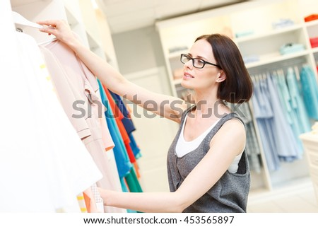 Cheerful young saleswoman selecting clothes in shop - stock photo