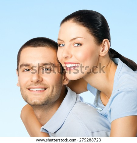 Cheerful young smiling attractive couple, on blue sky background - stock photo