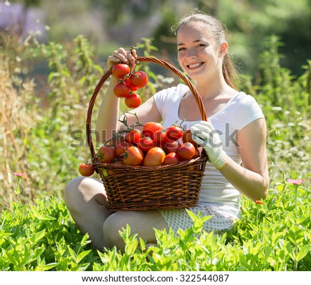 Cheerful young smiling woman with tomato harvest in garden - stock photo