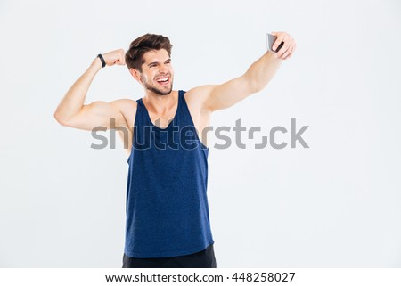 Cheerful young sportsman showing biceps and taking selfie with smartphone over white background - stock photo