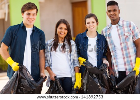cheerful young teenage volunteers with garbage bag - stock photo