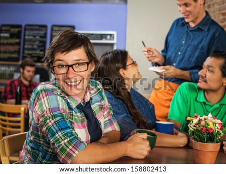 Cheerful young white female with friends in coffee house - stock photo