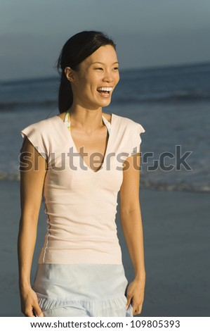 Cheerful young woman enjoying on a beach - stock photo