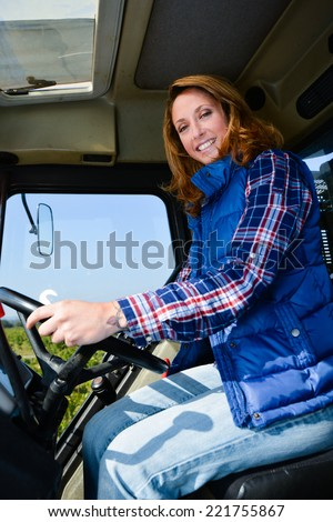 cheerful young woman farmer driving tractor in the fields during harvest in countryside - stock photo
