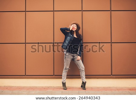 cheerful young woman full-length standing against a wall. copy-space - stock photo