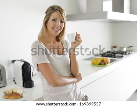 Cheerful young woman having coffee in kitchen - stock photo