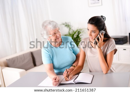 cheerful young woman helping an old person doing paperwork and telephone call - stock photo