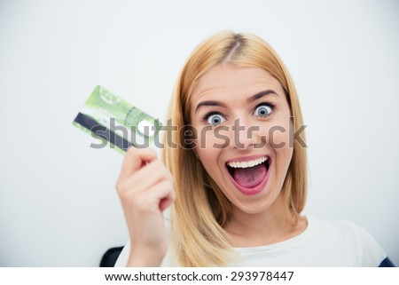 Cheerful young woman holding bank card over gray background - stock photo