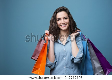 Cheerful young woman holding colorful shopping bags and smiling at camera - stock photo