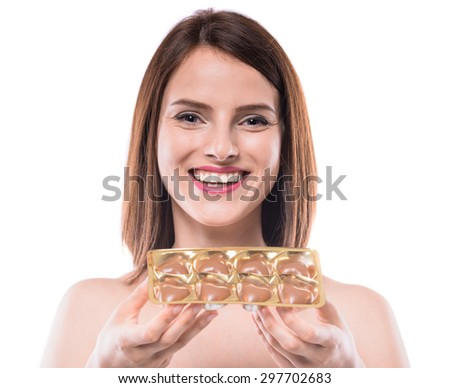 Cheerful young woman holding delicious chocolate candies over white background. - stock photo