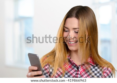 Cheerful young woman holding mobile phone  - stock photo