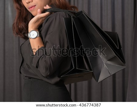 Cheerful young woman holding shopping bags  - stock photo