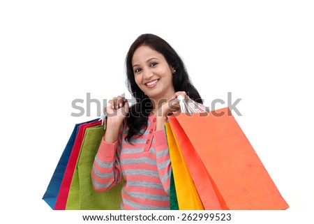Cheerful young Woman holding shopping bags against white background - stock photo