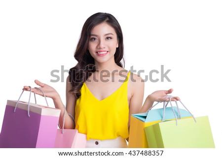 Cheerful young woman holding shopping bags. Beautiful young Asian shopper smiling happy. - stock photo