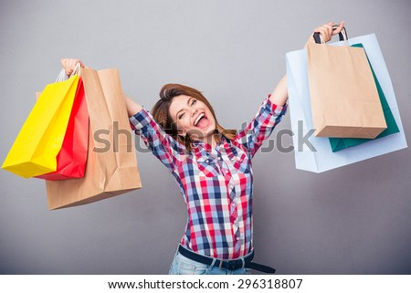 Cheerful young woman holding shopping bags over gray background. Looking at camera - stock photo