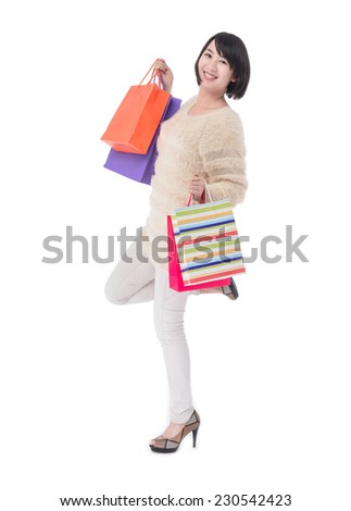 Cheerful young woman holding shopping bags posing - stock photo