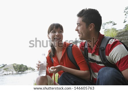 Cheerful young woman holding waterbottle by a man outdoors - stock photo