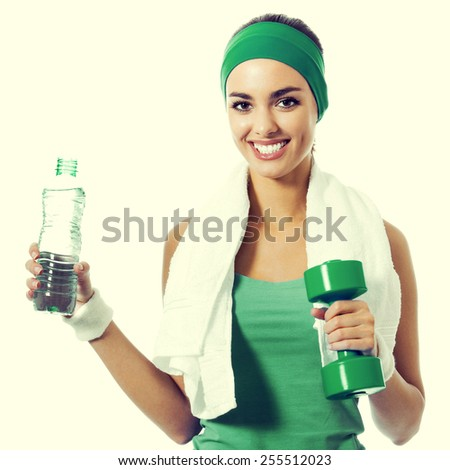 Cheerful young woman in green fitness wear with dumbbell and water - stock photo