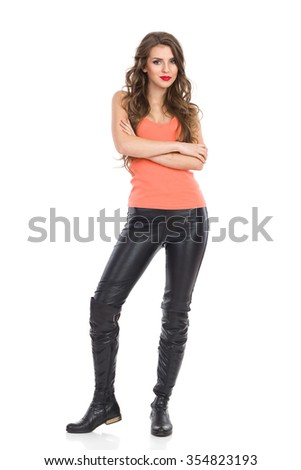 Cheerful young woman in orange shirt standing with arms crossed and looking at camera. Full length studio shot isolated on white. - stock photo