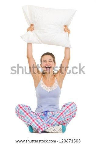 Cheerful young woman in pajamas sitting and holding pillow - stock photo