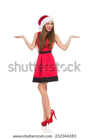 Cheerful young woman in santa's hat standing on one leg with arms outstretched. Full length studio shot isolated on white. - stock photo