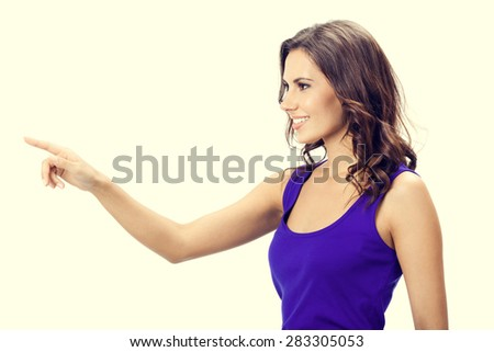 Cheerful young woman in violet smart casual clothing, showing copyspace, visual imaginary or something, or pressing virual button - stock photo