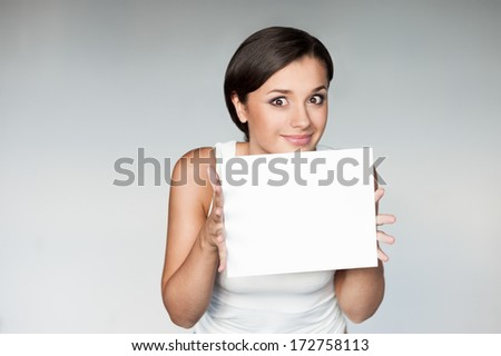 cheerful young woman in white singlet holding sign over gray background - stock photo