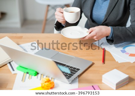 Cheerful young woman is enjoying hot drink - stock photo