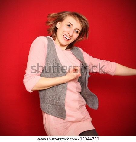 cheerful young woman jumping in front of red background - success - stock photo