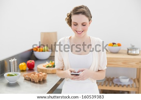 Cheerful young woman messaging with her smartphone standing in the kitchen at home - stock photo