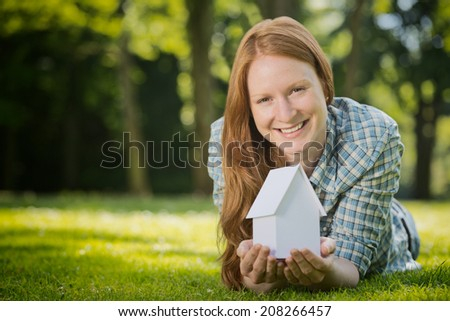 Cheerful young woman on an empty property holds a white paper house in her hands. Copy space available. - stock photo